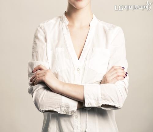흰색 셔츠를 입고 팔짱을 낀 여자의 정면 사진