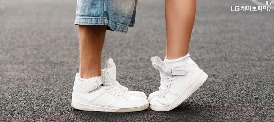 똑같은 색과 모양의 커플 운동화를 신고 마주 서있는 남자와 여자의 다리
