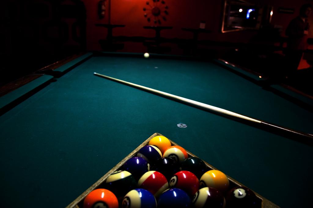 포켓볼 테이블 위에 놓인 공과 큣대