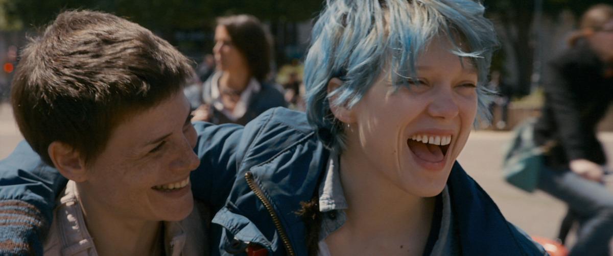 푸르게 염색한 숏컷의 여주인공이 여자친구와 어깨동무를 하고 웃고 있다, 영화 '가장 따뜻한 색, 블루' 속 한 장면ⓒ네이버 영화