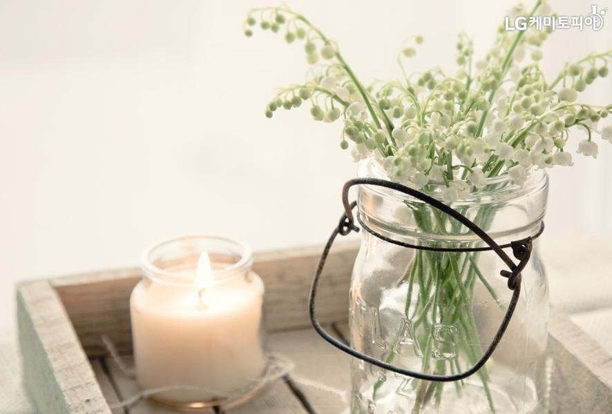 원목 테이블 위에 불 붙으 초와 흰색 꽃다발이 담긴 화병있다.