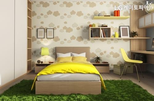 무늬가 그려진 벽지와 노란색 포인트 컬러를 이용한 아늑한 침실 전경
