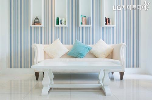 하늘색 톤 거실에 흰색 소파가 놓여져 있고 흰색 하늘색 쿠션이 함께 있다.