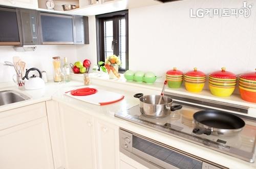 깔끔한 흰색 위주의 주방에 빨강, 노랑색의 식기가 놓여져 있다.