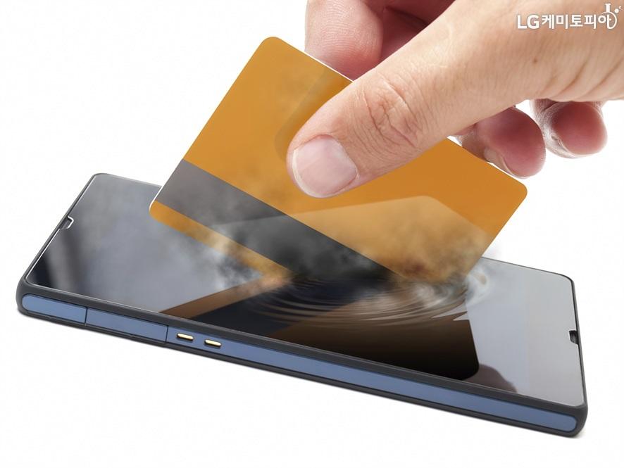 휴대폰 안에 신용카드를 삽입하고 있는 이미지컷. 신용카드가 모바일에 심겨졌다는 의미를 반영하고 있다.