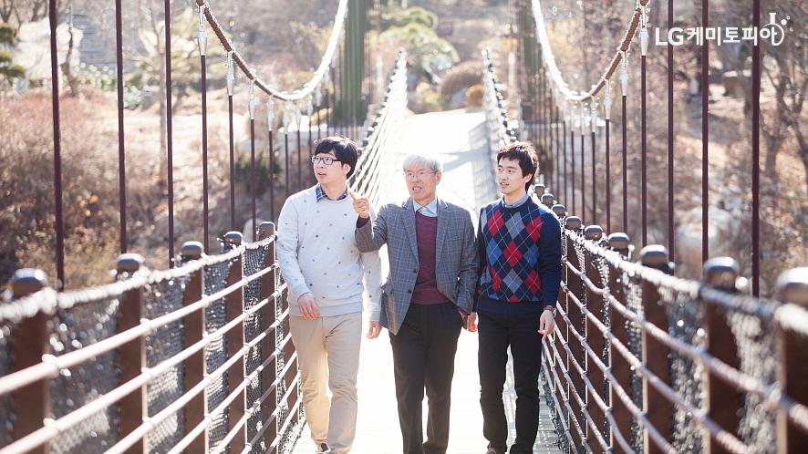 수목원을 가로지르는 다리 위를 거니는 세 사람