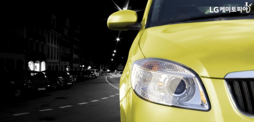 어두운 도로 위를 달리는 노란색 자동차의 전면이 클로즈업된 사진