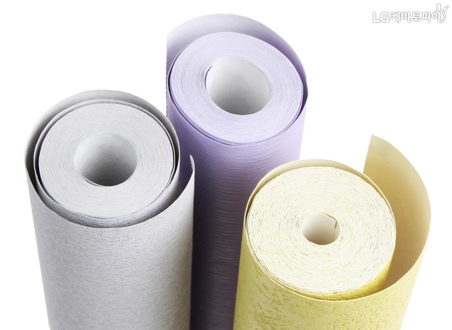노랑, 보라, 흰색 계열의 서로 다른 소재의 벽지 두루마리