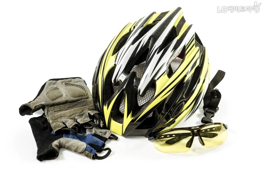 노란색과 검정색이 조합된 자전거 헬멧과 장갑 그리고 노란색 선글라스가 함께 있는 사진.