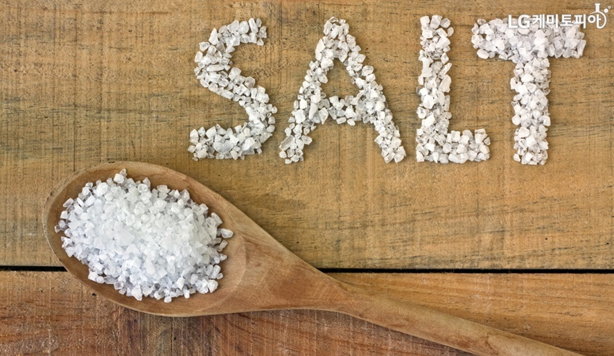 나무 수저에 소금이 담겨있고 SALT라고 쓰여있다.