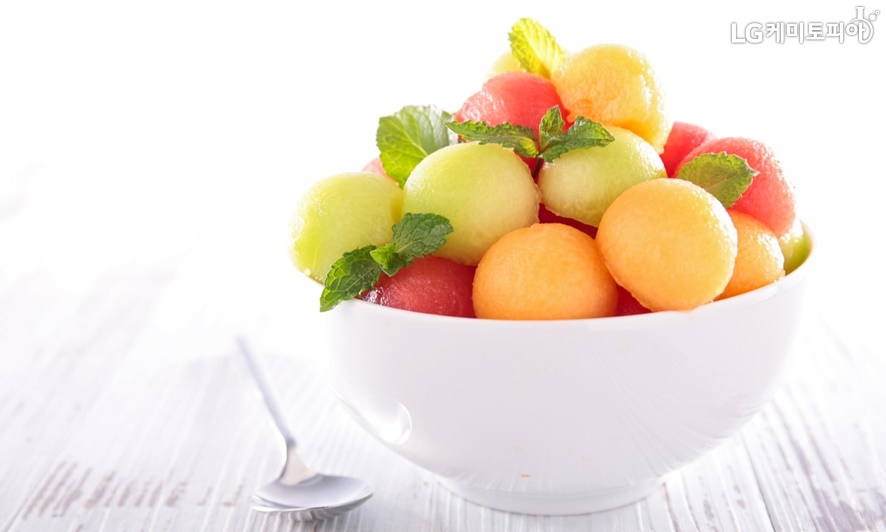 알록달록 동그랗고 차가운얼음 아이스크림이 과일과 섞여 하얀 그릇에 담겨 있다.