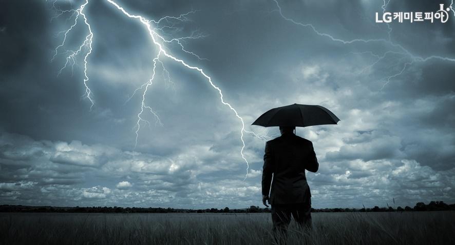 번개(낙뢰)치는 하늘을 보고 있는 우산 쓴 남자의 뒷모습