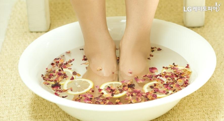 꽃잎이 뿌려진 그릇에 발을 담가 족욕을 하는 발