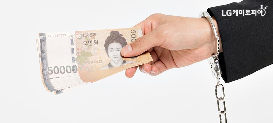 지폐를 들고 있는 손목에 수갑이 채워져있다.