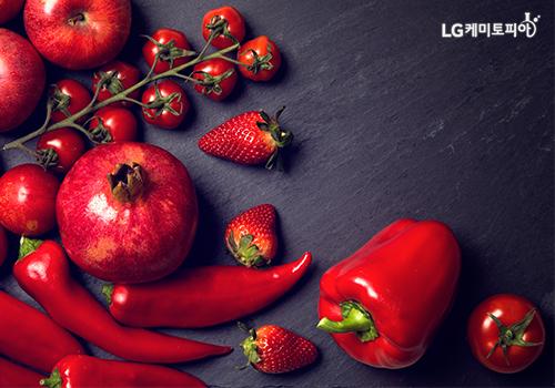 빨간색 고추, 딸기, 석류 등이 바닥에 놓여있다.