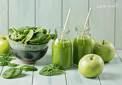 녹색 사과, 채소가 있고, 그 옆에 투명한 유리병에 녹색주스가 담겨있다.