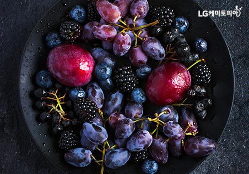 블루베리와 아로니아 등 검은색과 보라색의 채소와 과일이 원형 접시에 담겨있다.