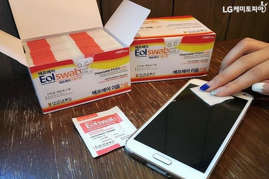 일회용 알콜솜인 에프에이 이올스왑 제품으로 스마트폰 액정을 닦고 있다.