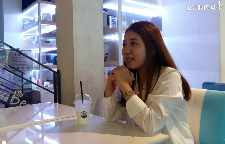 흰 색 블라우스를 입고 긴 생머리인 여성이 양 팔을 테이블 위에 올려두고 있다. 테이블 위에는 음료가 있다.