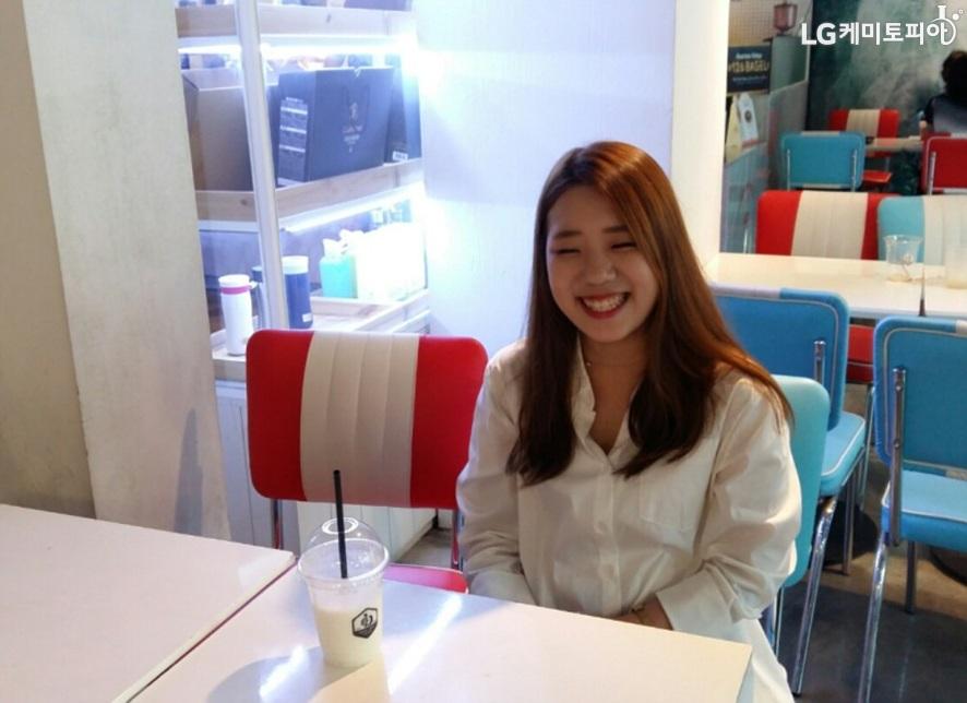 흰 색 블라우스를 입고 긴 생머리인 여성이 환하게 미소를 짓고 있다. 테이블 위에는 음료가 있다.