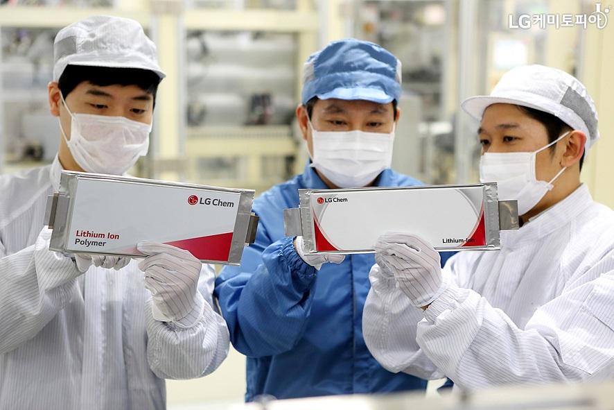 LG화학 남성직원 3명이 연구용 모자와 마스크, 가운, 장갑을 착용하고 제품을 손에 들고 검사하고 있다.