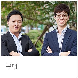 구매팀 남자 직원 두 분이 미소를 짓고 나란히 서있다.