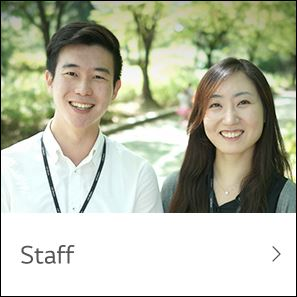 Staff 남녀 직원 두 분이 야외 푸른 숲 길에서 활짝 웃고 계신다.