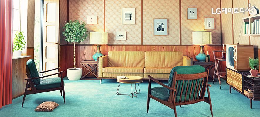 인테리어-창문이 있는 거실에 쇼파와 의자가 있고 노랑색 벽지 위에 액자들이 걸려 있다.