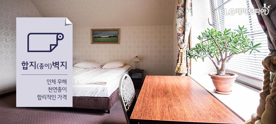 합지(종이)벽지- 인체 무해/천연종이/합리적인 가격:합지(종이)벽지가 적용된 창문이 있는 방, 옅은 컬러의 벽지, 침대 머리 맡 벽에 걸린 액자가 있다.