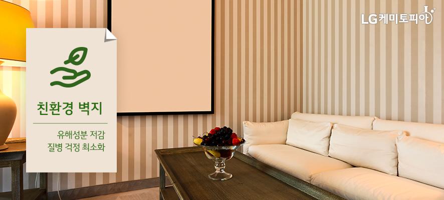 친환경 벽지 - 유해성분 저감/ 질병 걱정 최소화:친환경 벽지가 적용된  골드색의 세로 스트라이프 줄무늬 벽지, 연베이지색 쇼파, 티테이블, 스텐드가 있다.