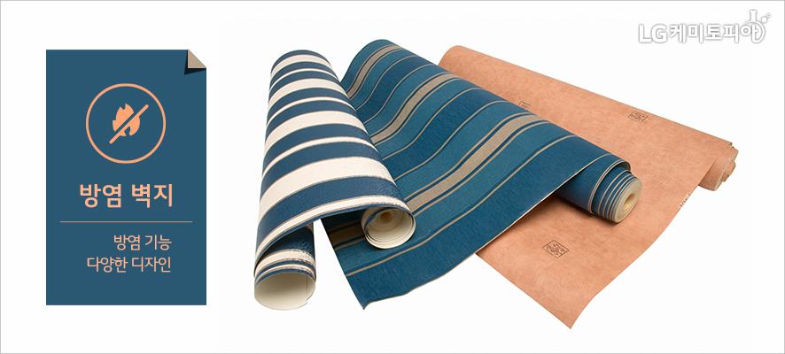 방염 벽지 - 방염 기능/다양한 디자인 :방염 벽지가 적용된 방 푸른계열의 스트라이프 포인트벽지와 황토색 민무늬 벽지가 롤로 말려져 있다.