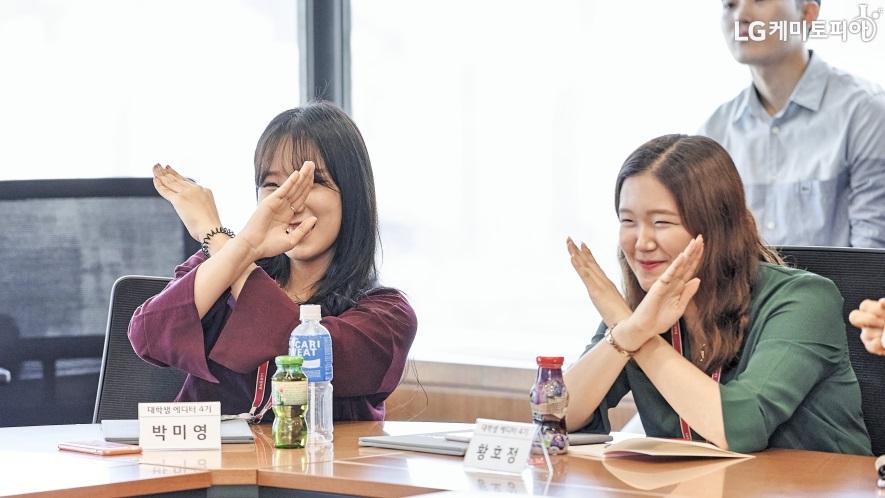LG화학 대학생 에디터 4기 중 박미영 에디터와 황효정 에디터가 손으로 x자를 들고 있다.
