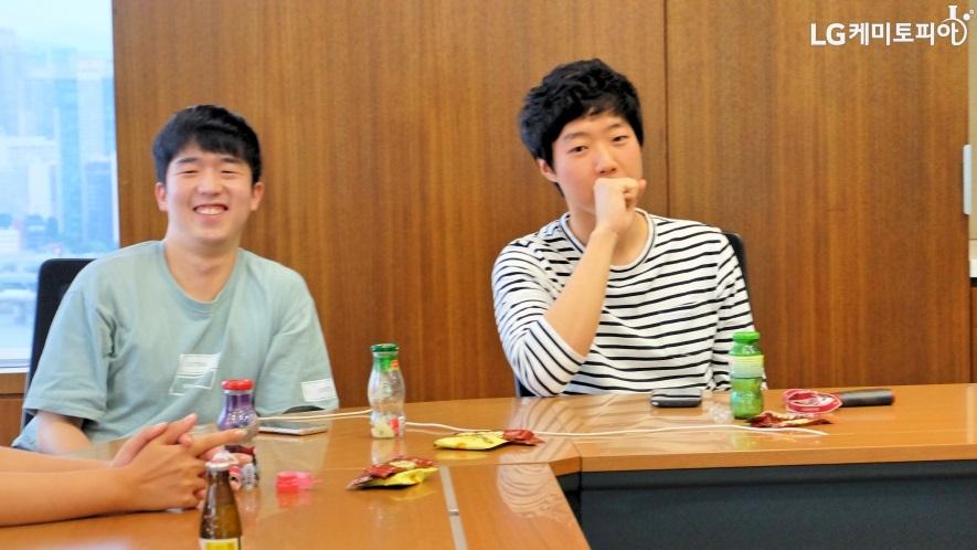 LG화학 대학생 에디터 3기, 양태현 에디터와 진재훈 에디터가 테이블에 앉아 웃고 있다.