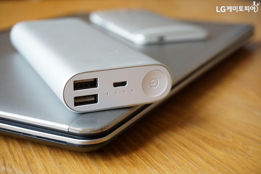 휴대용 전자기기(노트북과 휴대폰 보조배터리)가 놓여있다.