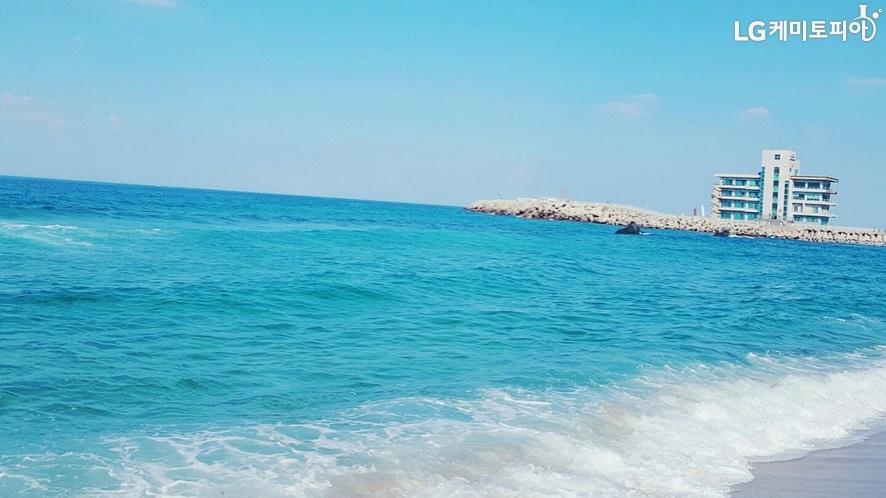 파란 하늘 아래 푸른색의 넓은 바다가 있고, 파도가 치고 있는 모습. 우측 위로는 방파제가 있고 건물 한 채가 있다.