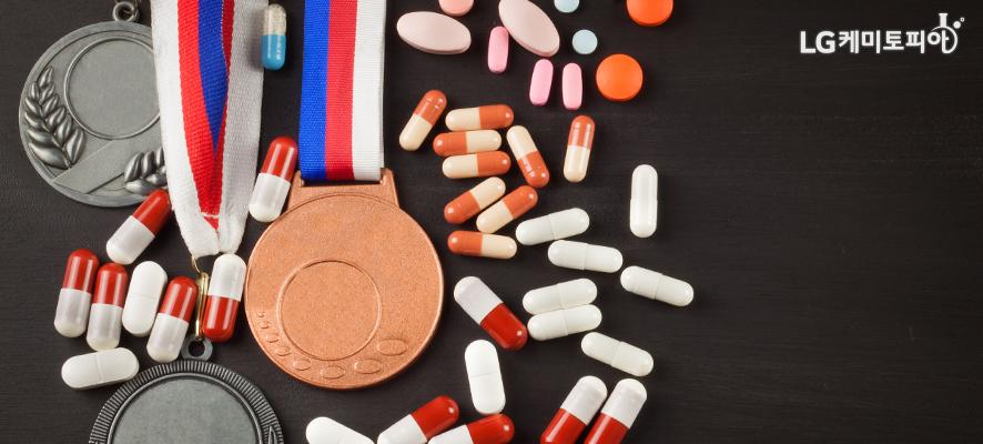 캡슐 알약들이 종류별로 쏟아져 있고 그 사이사이에 금은동 메달이 있다.