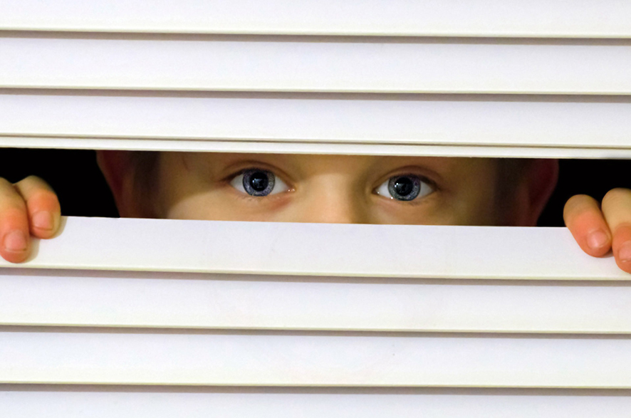 창문의 블라인드 틈 사이로 남자아이가 밖을 내다보고 있다.