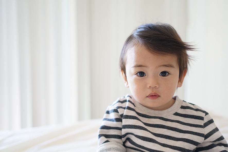 스트라이프 티를 입은 아기가 앉아있다.