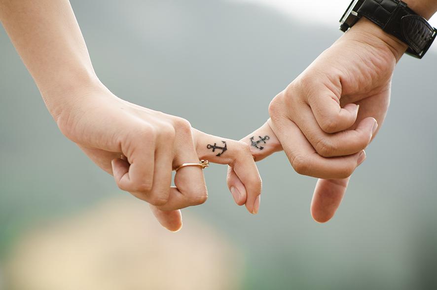 남자와 여자가 서로 손가락을 걸고 있다.