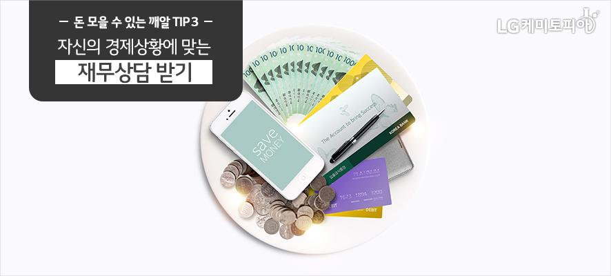 돈 모을 수 있는 깨알 TIP 3:자신의 경제상황에 맞는 재무상담 받기(그릇 위에 돈 관리 어플이 보이는 스마트폰과 지폐 돈과 동전, 통장, 볼펜 등이 놓여있다.)