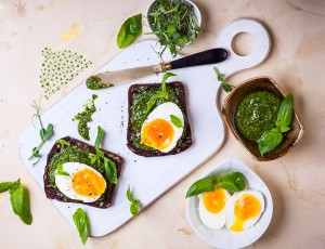도마 위에 식빵이 2장 올려져 있고 , 식빵위로 녹색쩀과 계란후라이가 있다.