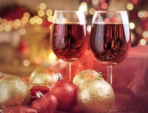 붉은색 테이블 위에 크리스마스 느낌의 장식이 되어있고, 와인잔 2잔에 레드와인이 있다.