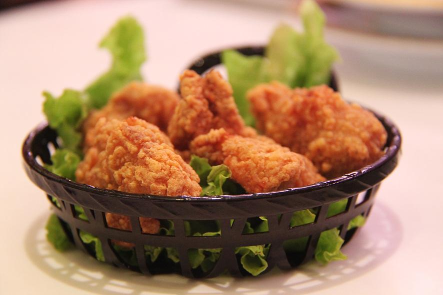 바구니에 바삭바삭해 보이는 튀김옷이 입혀진 후라이드 치킨이 담겨있다.