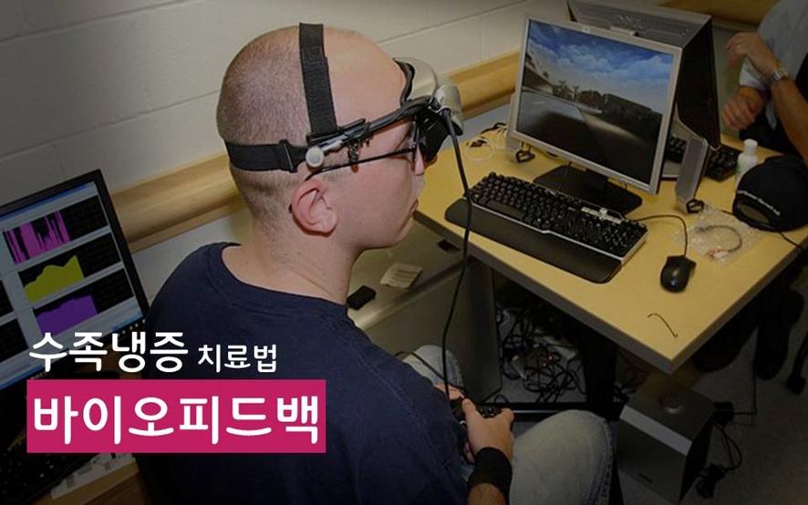 수족냉증 치료법 '바이오피드백'(데스크탑과 키보드, 마우스가 놓여있는 책상 앞에 앉은 남자가 머리에 장치를 쓰고 있다.)