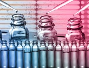 실험용 유리병에 스포이드로 액체를 떨어뜨리고 있다.