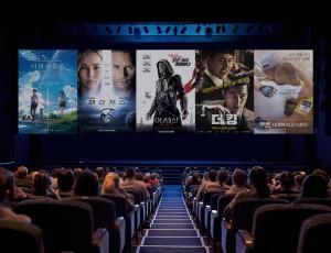 영화관 스크린에 개봉 예정 영화 포스터 5개가 보인다.