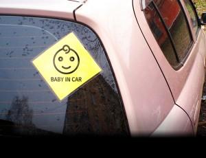 자동차 뒷유리에 Baby in car 표시 스티커가 붙어 있다.