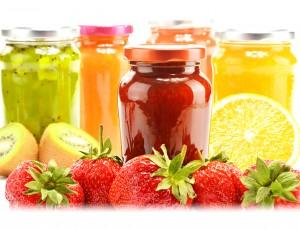 투명한 유리병 안에 여러 종류의 과일청이 들어있고 그 앞쪽에 과일들이 있다.