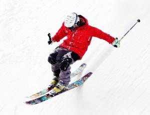 스키장비를 완장한 사람이 스키를 타며 눈 쌓인 스키장을 내려오고 있다.