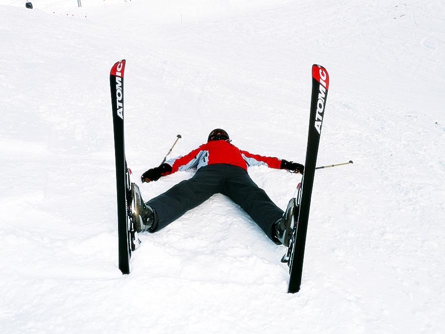 눈 쌓인 땅 위에 스키 장비를 착용한 사람이 엎드려서 누워있다.